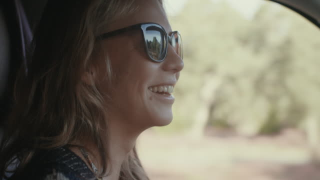 Young woman with sunglasses driving van through pine forest in South of France laughing.