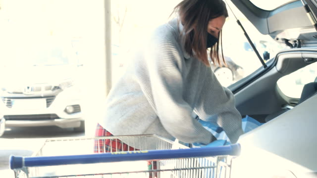 young woman with surgical masks packing groceries from supermarket in car trunk - conservation stock videos & royalty-free footage