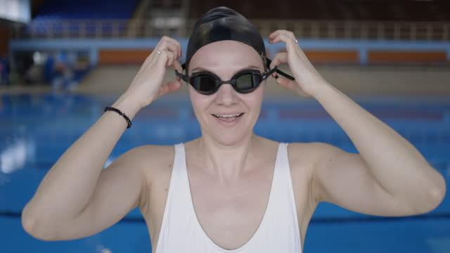 young woman with swimming cap standing on poolside and putting on swimming googles - swimming cap stock videos & royalty-free footage