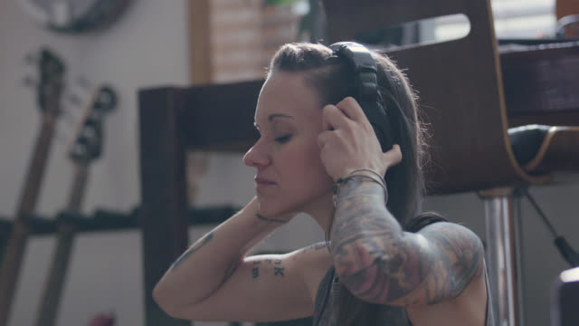ms. young woman with tattoos puts on headphones and listens to music in apartment studio. - body positive stock videos & royalty-free footage