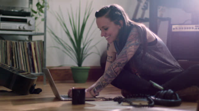 WS. Young woman with tattoos smiles as she works on laptop computer on apartment floor.