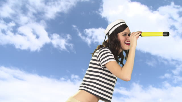 vidéos et rushes de young woman with telescope, pointing and smiling - marinière