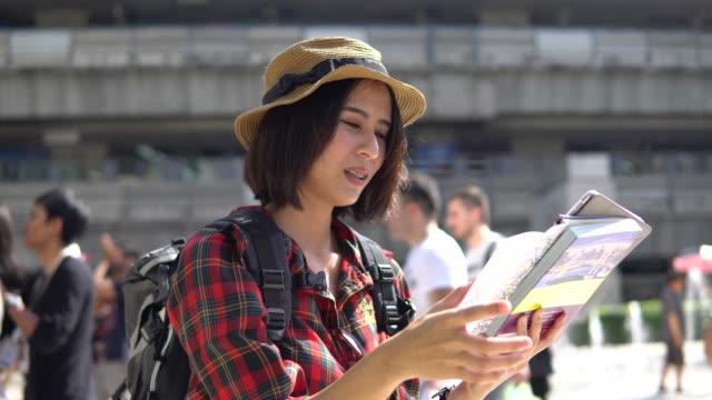 stockvideo's en b-roll-footage met jonge vrouw met toeristische kaart - verdwaald