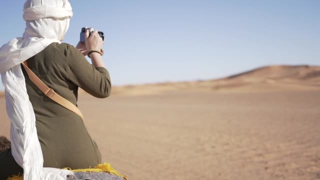 young woman with turban on a camel in the dunes of the sahara desert - photographer stock videos & royalty-free footage