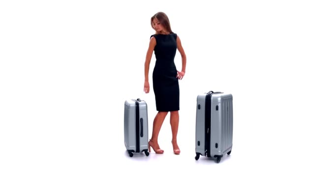 Young woman with two suitcases waiting and sitting