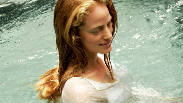 Young woman with wet hair in a pool