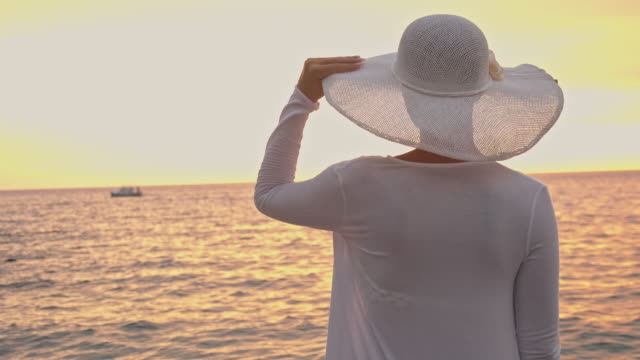 slo mo young woman with white hat watching the sunset - hat stock videos and b-roll footage
