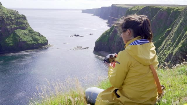 young woman with yellow raincoat on a cliff in scotland using her photo camera - scotland stock videos & royalty-free footage