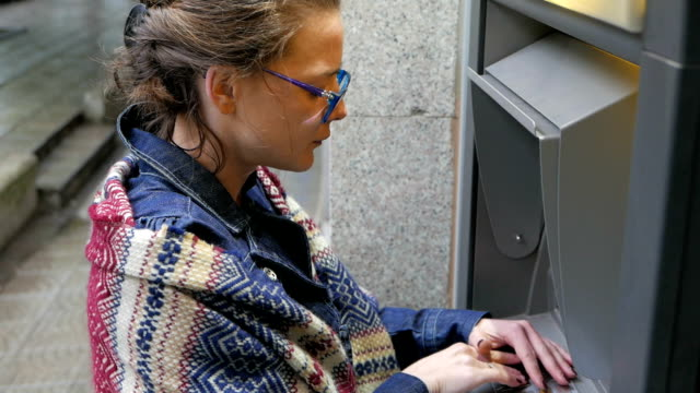 Young woman withdrawing money from ATM machine