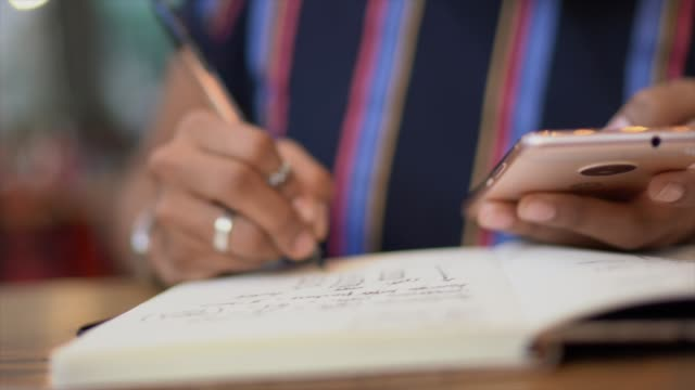 vídeos de stock, filmes e b-roll de mulher nova que trabalha e que usa o portátil ao escrever em um bloco de notas - caneta