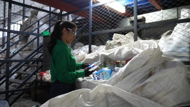 Jonge vrouw die werkt op een recyclingcentrum scheiden van plastic flessen in verschillende containers en zakken