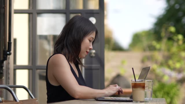young woman working at cafe with laptop - non us film location stock videos & royalty-free footage