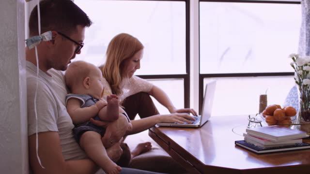 vídeos de stock, filmes e b-roll de jovem mulher que trabalha no seu computador enquanto sua filha e marido assistir - aluno mais velho