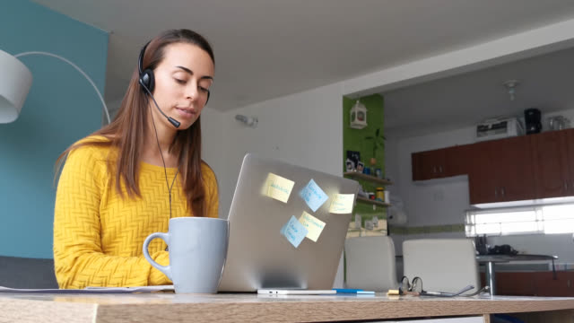 vídeos de stock e filmes b-roll de young woman working at home as a customer service representative wearing a headset while typing on laptop - call center