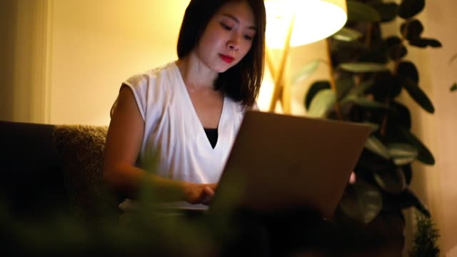 young woman working from home with laptop at night - waist up stock videos & royalty-free footage