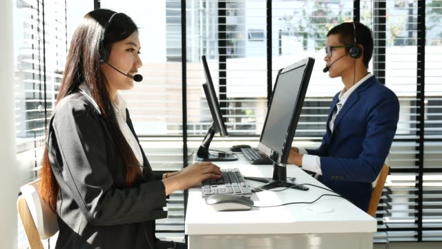 Young woman working in a call center using a headset with team