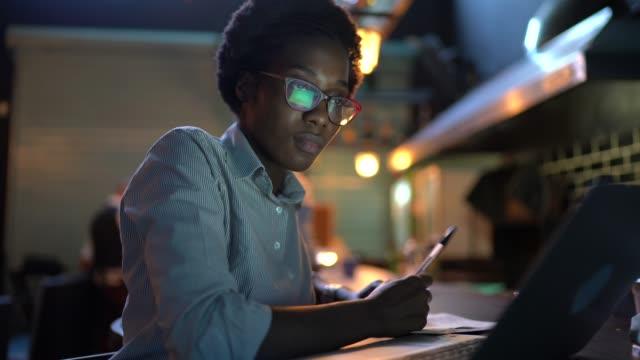 vídeos de stock, filmes e b-roll de jovem trabalhando em um restaurante, usando laptop - controle