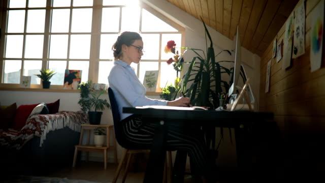 junge frau arbeitet im büro - arbeitszimmer stock-videos und b-roll-filmmaterial
