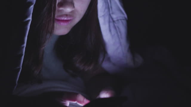 Young woman working late in bed.