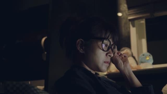 stockvideo's en b-roll-footage met jonge vrouw die werkt laat in de nacht. - leesbril