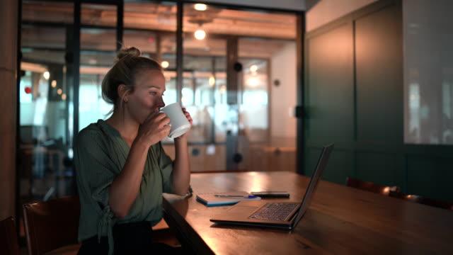 vídeos y material grabado en eventos de stock de joven trabajando hasta tarde en el cargo - taza de café