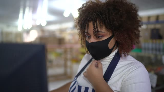 young woman working looking to monitor at store - wearing face mask - apron stock videos & royalty-free footage