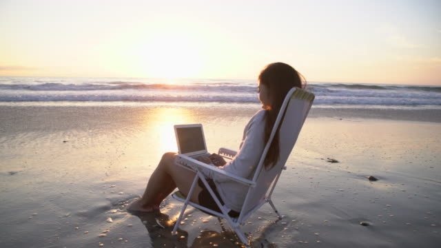 WS Young woman working on a laptop by the beach.