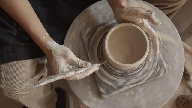 cu young woman working on a pottery wheel in her ceramics studio - 陶器点の映像素材/bロール