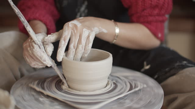 vídeos de stock e filmes b-roll de cu young woman working on a pottery wheel in her ceramics studio - cerâmica
