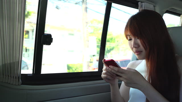 Young woman working on a van typing a message on her mobile phone.
