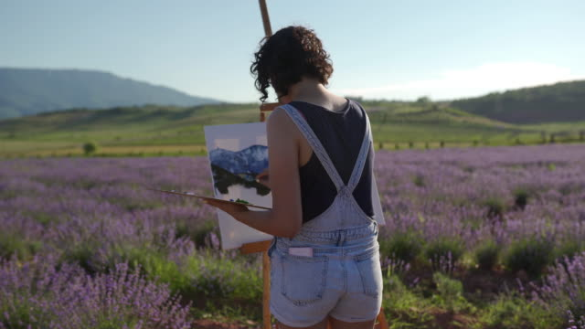 young woman working on abstract painting at lavender field - artist stock videos & royalty-free footage