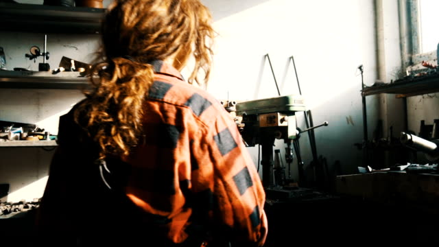 Young woman working on drilling machine in a workshop