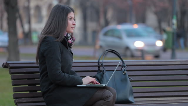 Young woman working on her laptop outdoor.