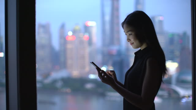 ms young woman working on her phone by a window, shanghai, china - chinese ethnicity stock videos & royalty-free footage