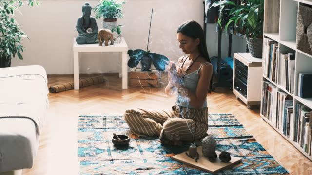 junge frau arbeitet an ihrer spiritualität, während sie zu hause meditiert - gebetsposition stock-videos und b-roll-filmmaterial