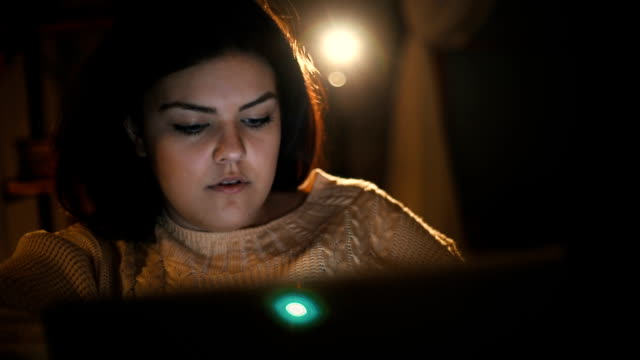 Junge Frau, die auf laptop zu Hause fühlen