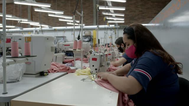 vídeos y material grabado en eventos de stock de mujer joven que trabaja en la línea de producción de camisetas rosas todas con máscaras protectoras en una fábrica textil - fábricas tradicionales
