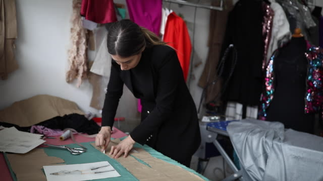 young woman working on the sewing workshop - fashion designer stock videos & royalty-free footage