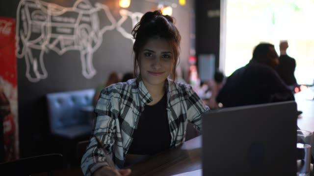 vídeos de stock, filmes e b-roll de jovem trabalhando ou estudando em um bar, usando laptop - trabalho de freelancer