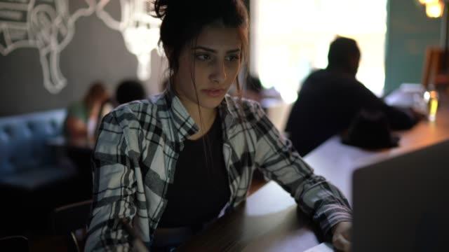 vídeos de stock, filmes e b-roll de jovem trabalhando ou estudando em um bar, usando laptop - estudante universitária