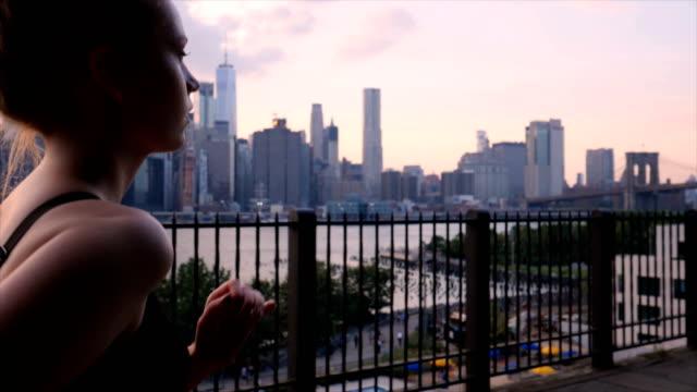 vídeos de stock, filmes e b-roll de jovem mulher malhando contra o pôr do sol à beira-mar de nova york - distrito financeiro de manhattan