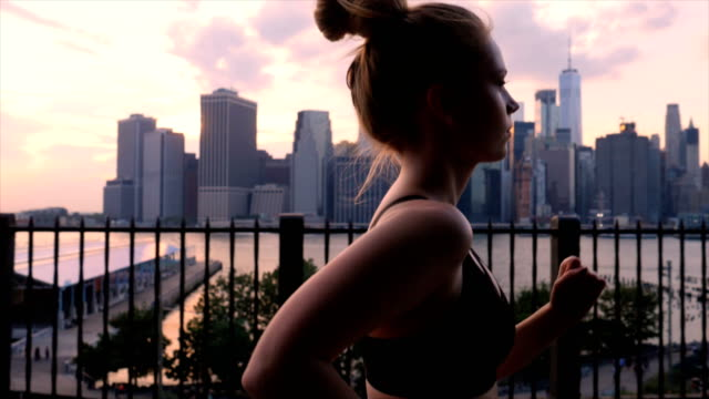Young woman working out against the New York City waterfront sunset