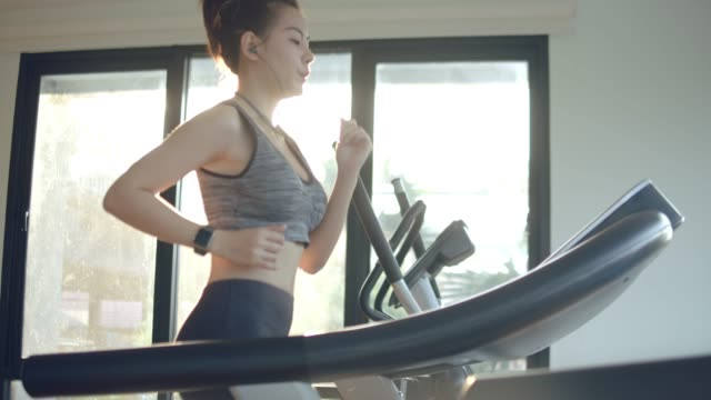 young woman working out and jogging on treadmill at gym - gym stock videos & royalty-free footage