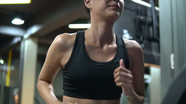 young woman working out and jogging on treadmill at gym - cross trainer stock videos & royalty-free footage