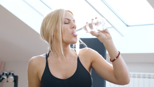Young woman working out: gym/Pilates/Yoga/Bootcamp. And drink water