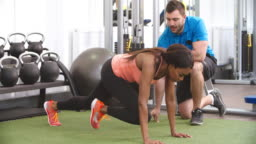Young woman working out in gym under supervision of trainer