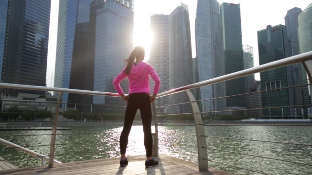 WS Young woman working out in the city at sunset.