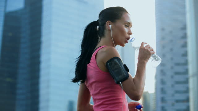MS Young woman working out in the city while listening to music.