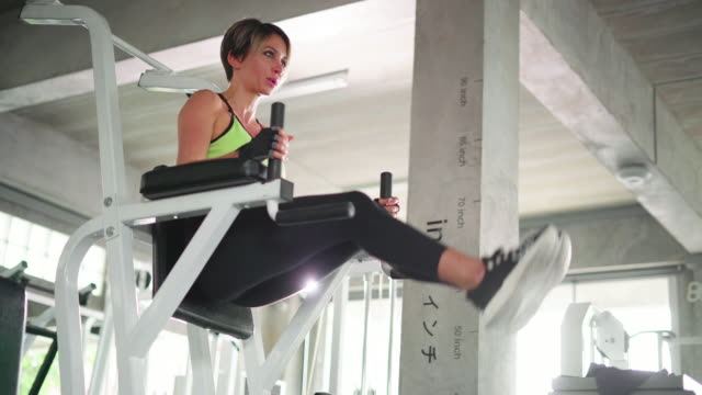 young woman working out on exercise machine - exercise machine stock videos & royalty-free footage