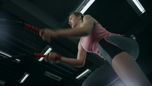 Young woman working out with battle ropes